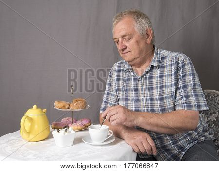 Mature man making a cup of tea whilst sitting down at a table