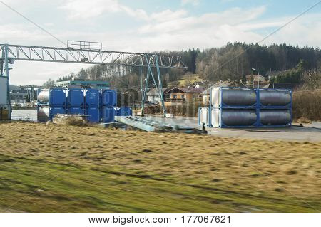 Gantry crane and production tanks. View from the window of a train on a trip across Europe.