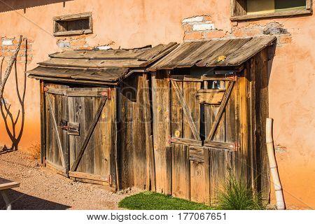 Two Vintage Western Storage Sheds On Side Of Adobe Building
