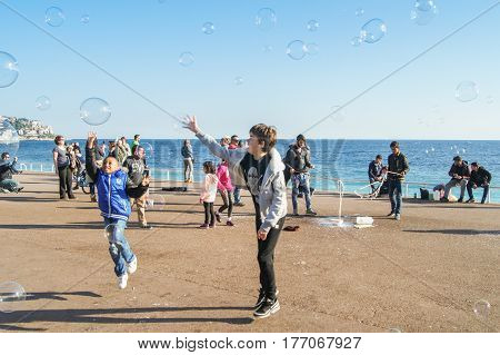 Nice, France - 25 February, Children in a jump catch soap bubbles, 25 February, 2017. People and tourists having a rest on the Cote d'Azur.
