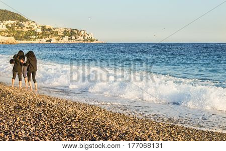 Nice, France - 25 February, Young people on the shore near the incoming wave, 25 February, 2017. People and tourists having a rest on the Cote d'Azur.