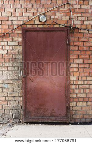 An Old Iron Door In An Brick Wall.