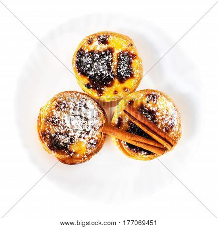 Delisious Egg Tarts with sweet curstard cream and cinnamon isolated on white background close up macro with sugar powder on a top. Portuguese Pasteis de Nata top view