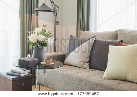 Vase Of Flower On Round Glass Table With Set Of Sofa In Modern Living Room