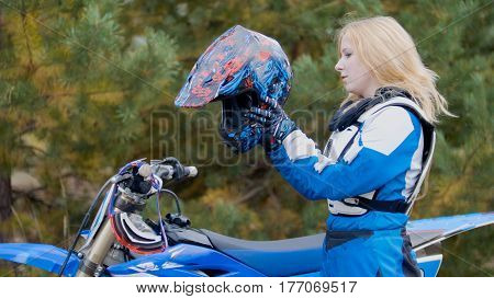 Blonde young Girl Bike wears a helmet - MX moto cross racing - rider on a dirt motorcycle, telephoto