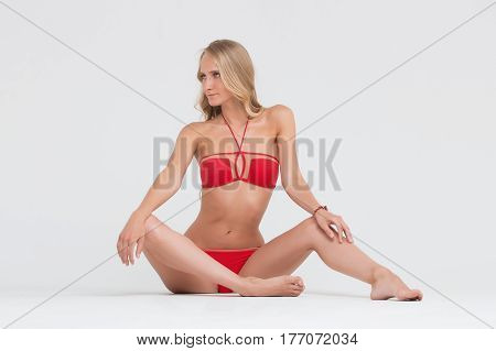 Girl with perfect body in red underwear on white background.