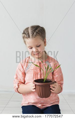 The child helps the plant to grow, the concept environment.
