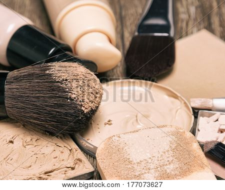 Makeup products to even out skin tone and hide imperfections: foundation, concealer, powder. Shallow depth of field
