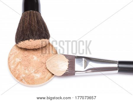 Round container filled with liquid foundation sprinkled with loose cosmetic powder and professional makeup brushes as clock hands on white background. Copy space