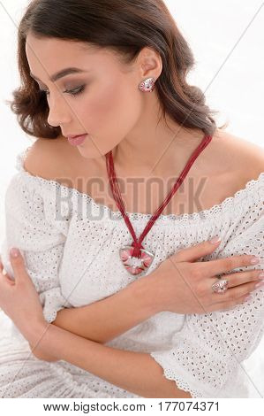 Young European attractive fashion model with long brown natural hair wearing luxury silver accessory and jewelry. Girl Isolated on white background