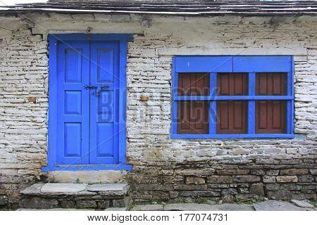 Grunge gray bricks wall with blue door and window of Nepali house