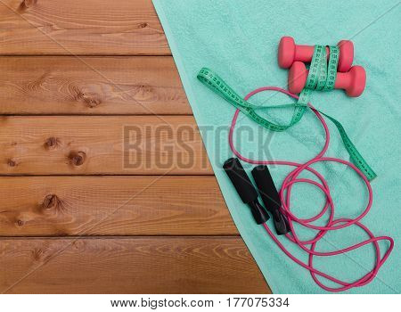 Fitness concept with dumbbells towel measure tape and skipping rope on wooden table background