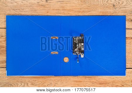 Open empty blue folder for storage of documents lying on a wooden table