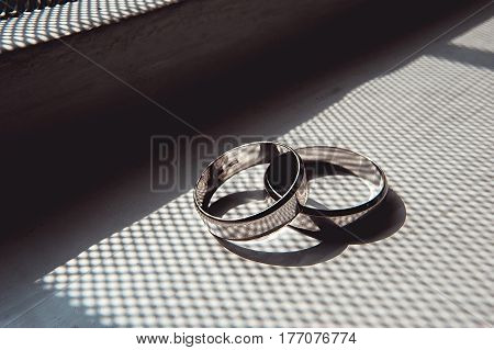 scrached wedding rings of white gold on a window sill in shadow in the form of cells