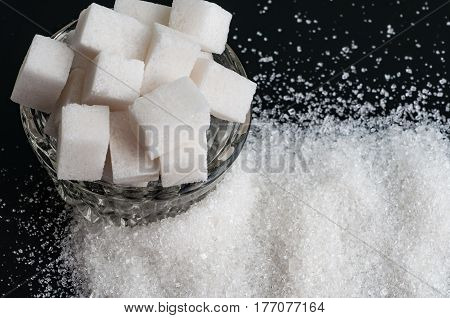 white granulated sugar and refined sugar on a black background