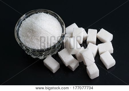Bowl of white sugar on black background top view