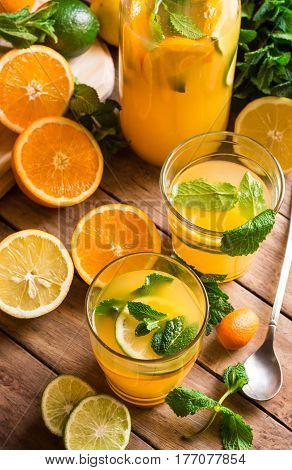 Citrus lemonade from lime oranges fresh mint in glasses and bottle cut fruits on kitchen table by window top view