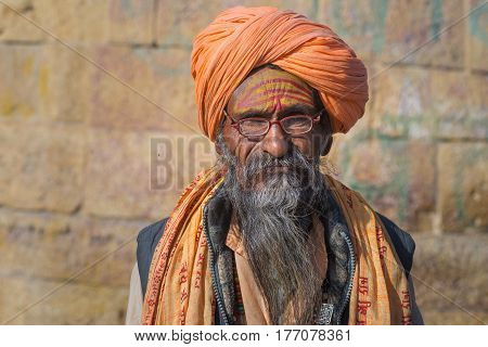 Jaisalmer India - March 2 2017: Sadhu portrait and close up at Jaisalmer Rajasthan India. The hindu spiritual guide and priest against ancient stone wall.