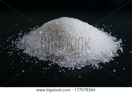 Heap of granulated white sugar on black surface