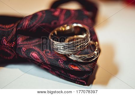 wedding rings wooden style on the black and red bowtie