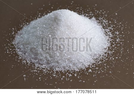 Heap of granulated white sugar on gray background