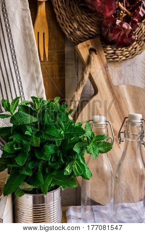 Provence rustic kitchen interior wood cutting board utensils glass bottles fresh herbs linen towel on white background authentic style kinfolk