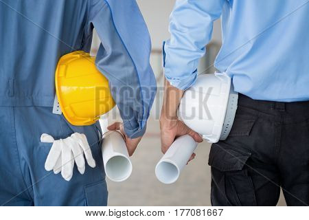 Close up back view of male construction worker and engineer holding roll of drawing and safety helmet indoor of construction site.