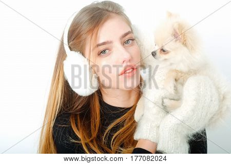 pretty girl or sexy woman with long blond hair hairstyle and adorable face in black bodysuit gloves mittens earmuffs holds small cute pomeranian spitz dog or puppy pet isolated on white background