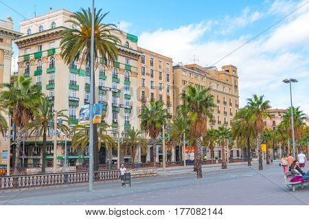 Barcelona, Spain, November 3rd, 2013.  Tourism in Europe, afternoon in Barcelona.  People enjoy the warm weather.   Palm tree-lined streets featuring cafes, shops, apartment & condo buildings, automobile & pedestrian traffic.