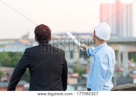 Businessmen and Asian Civil engineer in hardhats taking a look at the blueprint in urban environment