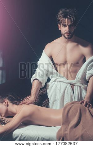 handsome bearded man of masseur therapist with muscular torso in white terry bathrobe makes massage for pretty woman or girl with sexy body in beauty spa salon