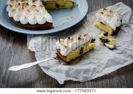 A piece of breton cake with plums and meringue on a wooden table