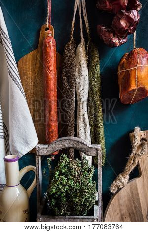 Variety of charcuterie sausages hanging on twine on hooks wood cutting bard herbs linen towel kitchenware pantry style rustic