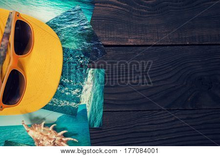 Sunglasses shell cap and pictures with the image of the sea on a wooden surface