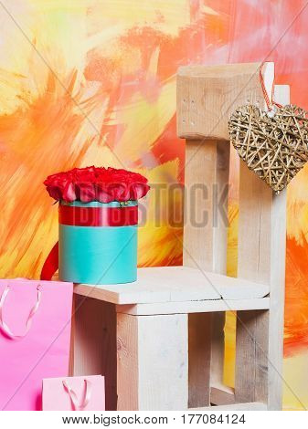 Beautiful red roses fresh natural flowers in blue present box with ribbon pink shopping bags or gift packages with valentines day heart on wooden chair on colorful abstract background copy space