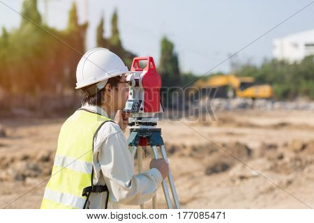 Land survey and Asian civil engineer working with his equipment.
