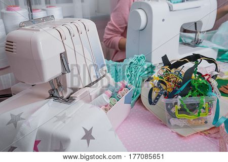 Sewing machine with many sewing utensils on a table close up