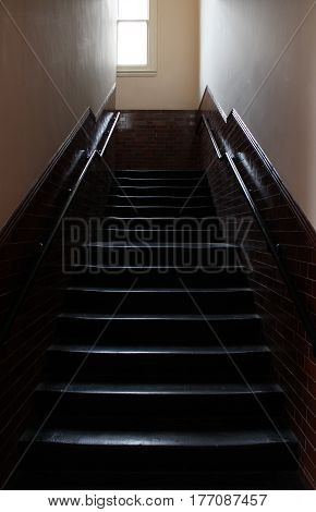 upwards shot of dark, creepy staircase of old school house in England