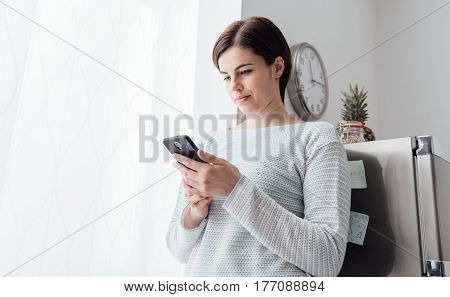 Young woman relaxing in the kitchen and texting with her smartphone