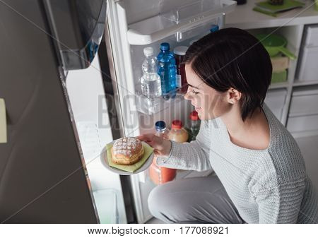 Woman Taking A Pastry Out Of The Fridge