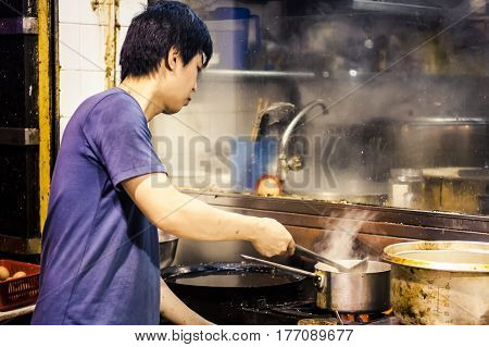 Hong Kong China - 8 June 2009: Man cooking vegetables in a pot of boiling water on the streetside in Mongkok district at night