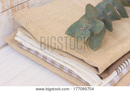 Stack of linen and cotton kitchen towels on white wood kitchen table branch of silver dollar eucalyptus on top close up