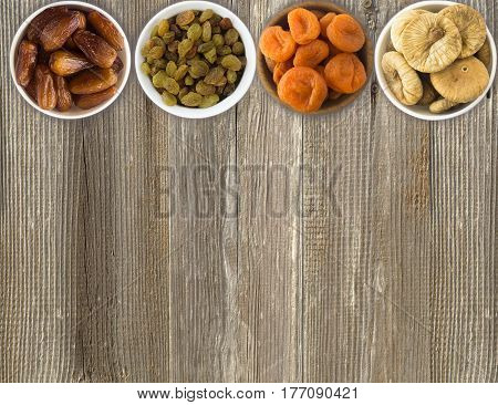 Dried fruit in a wooden bowls. Raisins dates dried apricots figs on a wooden background. Top view. Dried fruit with copy space for text.