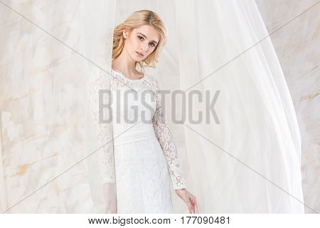 Portrait of the gorgeous thoughtful blonde bride with beautiful curly hair in a white wedding lacy dress. beautiful young model with bridal hairstyle and makeup in a wedding dress.