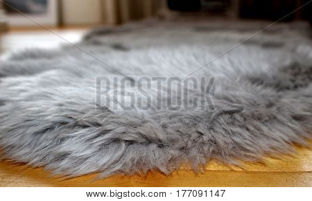 Close-up of fluffy grey faux fur floor rug on a wooden floor of young woman's house