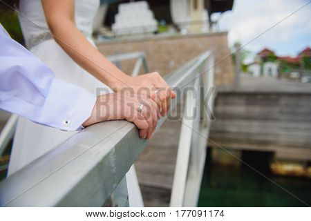 Hand of the bride and groom on wooden railing close-up. Focus on the ring of the groom.