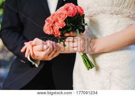 Groom and bride against the background of the river. Bride and groom holding hands close up. Black suit and white dress.