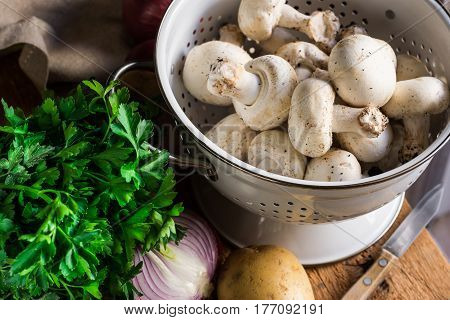 Fresh organic ingredients for preparing healthy vegetarian meal potatoes mushrooms in colander halved onion parsley knife on kitchen table top view