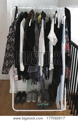 Contemporary white metal rack of clothes in modern flat with white hangers and wooden floor in dressing room / area