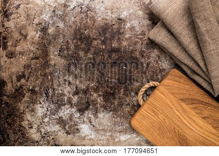 Wooden chopping board and kitchen towel on old rustic table